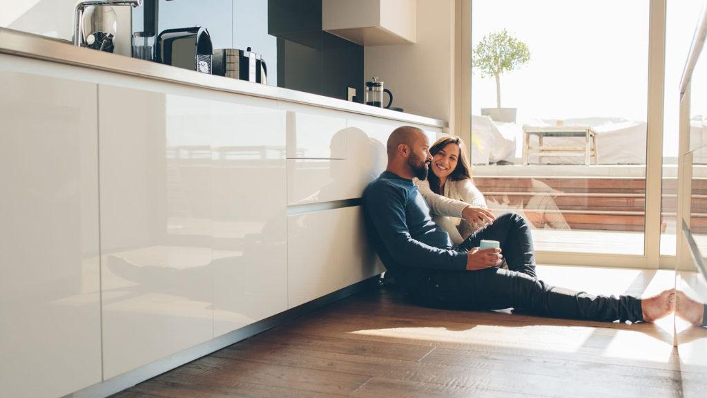 Couple Sitting on Hardwood Floors of Kitchen